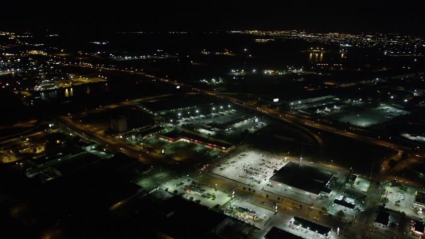 5K stock footage aerial video reverse view of a strip mall by the Danziger and I-10 High Rise Bridges at night, New Orleans, Louisiana Aerial Stock Footage | AX62_050