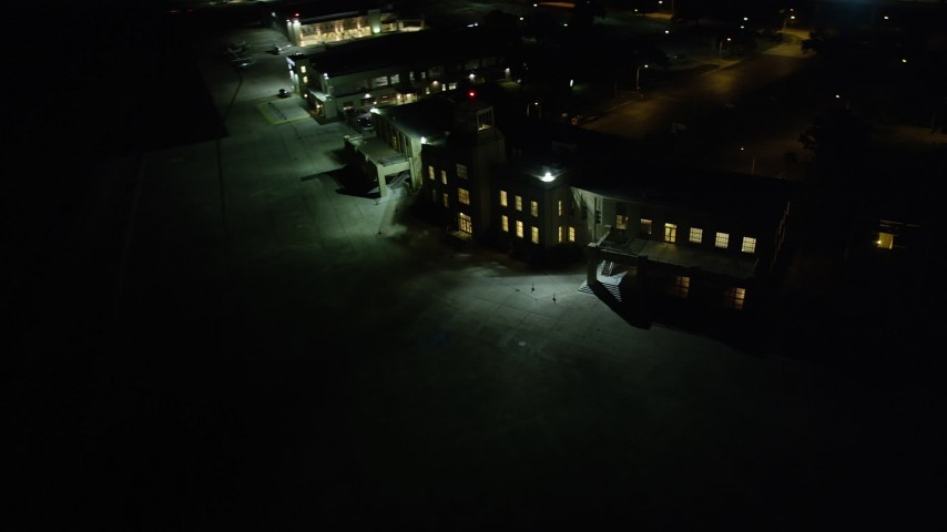 5K stock footage aerial video of the main terminal of New Orleans Lakefront Airport at night, Louisiana Aerial Stock Footage | AX62_052