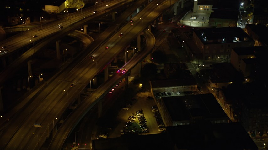 5K aerial video track an ambulance exiting the Crescent City Connection Bridge at night, New Orleans, Louisiana Aerial Stock Footage | AX63_012