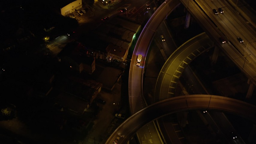 5K stock footage aerial video of an ambulance exiting the Crescent City Connection Bridge at night, New Orleans, Louisiana Aerial Stock Footage | AX63_013