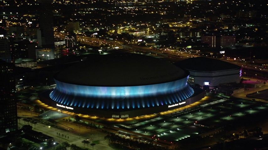 5K stock footage aerial video orbit the Superdome as it changes colors at night, New Orleans, Louisiana Aerial Stock Footage | AX63_020