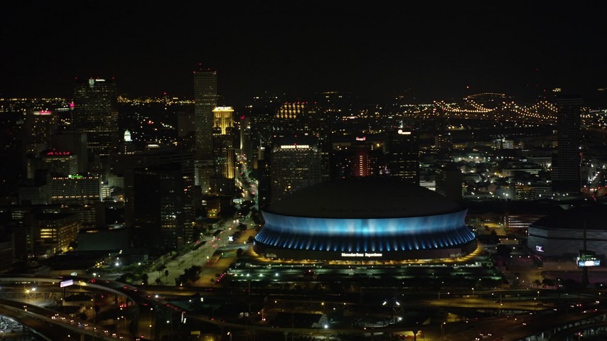 5K stock footage aerial video of the Superdome and Downtown New Orleans skyscrapers at night, Louisiana Aerial Stock Footage AX63_021