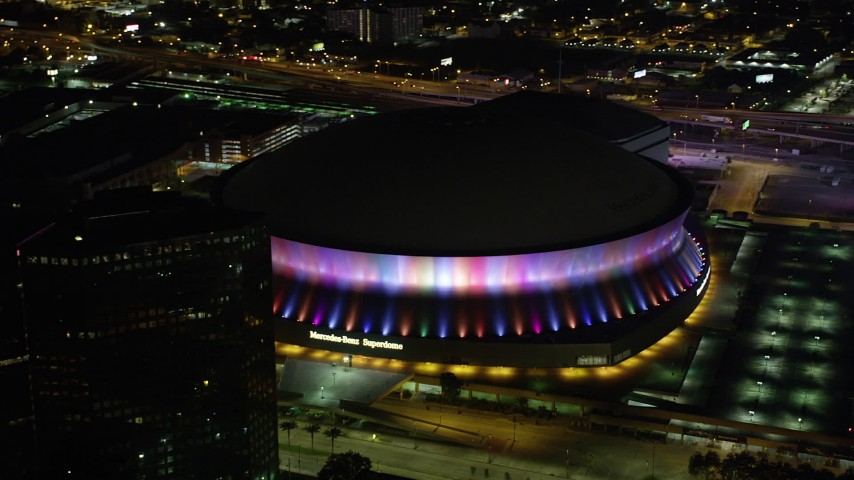 5K stock footage aerial video of orbiting the Superdome as the lights change colors at night, Downtown New Orleans, Louisiana Aerial Stock Footage | AX63_024