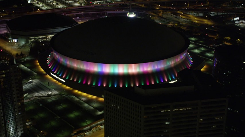 5K stock footage aerial video orbit the Mercedes-Benz Superdome at night and the lights change colors, Downtown New Orleans, Louisiana Aerial Stock Footage | AX63_025