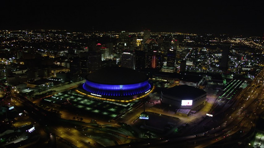 5K aerial video orbit Superdome and New Orleans Arena to reveal Downtown New Orleans skyscrapers at night, Louisiana Aerial Stock Footage | AX63_026