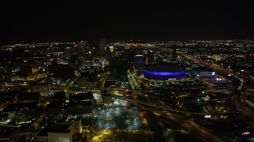 5K aerial video of a reverse view  Superdome and Downtown New Orleans at night in Louisiana Aerial Stock Footage | AX63_027