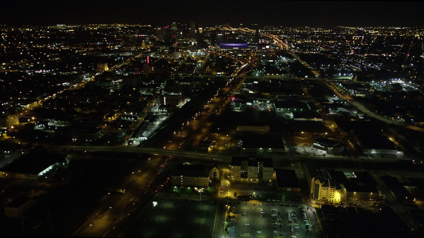5K stock footage aerial video pan across I-10 in Mid-City to reveal and approach Downtown New Orleans at night, Louisiana Aerial Stock Footage | AX63_038