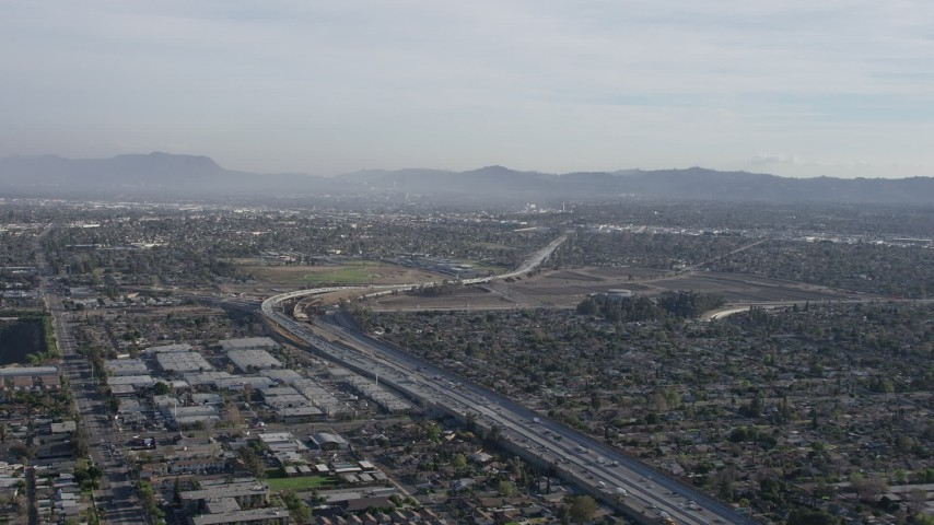 5K stock footage aerial video of I-5 / 170 split by warehouse buildings and suburban homes in Pacoima, California Aerial Stock Footage | AX64_0001