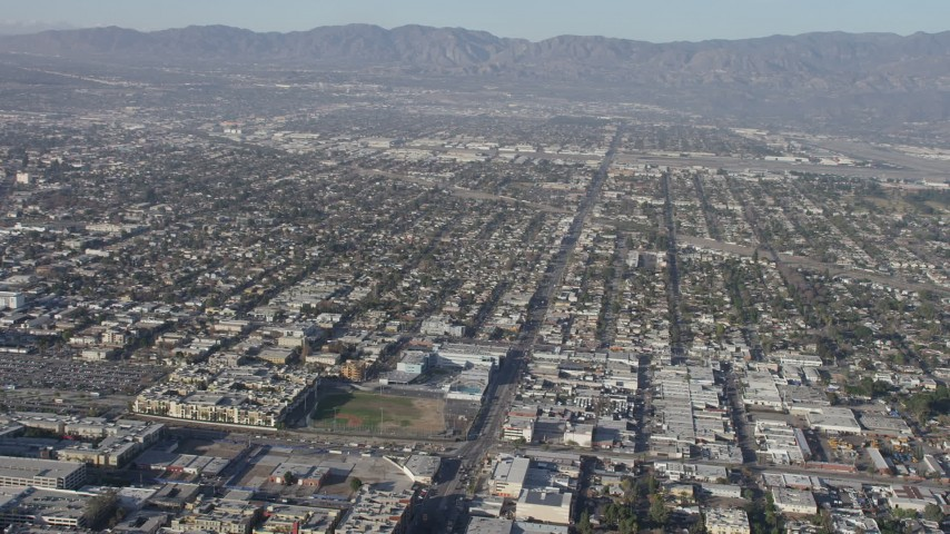 5K stock footage aerial video pan across suburban neighborhoods to reveal the Burbank Airport, California Aerial Stock Footage | AX64_0026