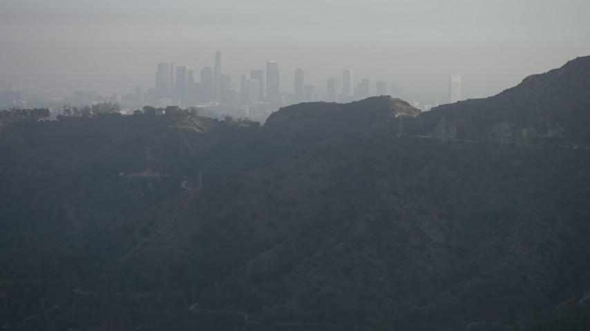 5K stock footage aerial video of hazy Downtown Los Angeles skyline seen from Hollywood Hills, California Aerial Stock Footage | AX64_0068
