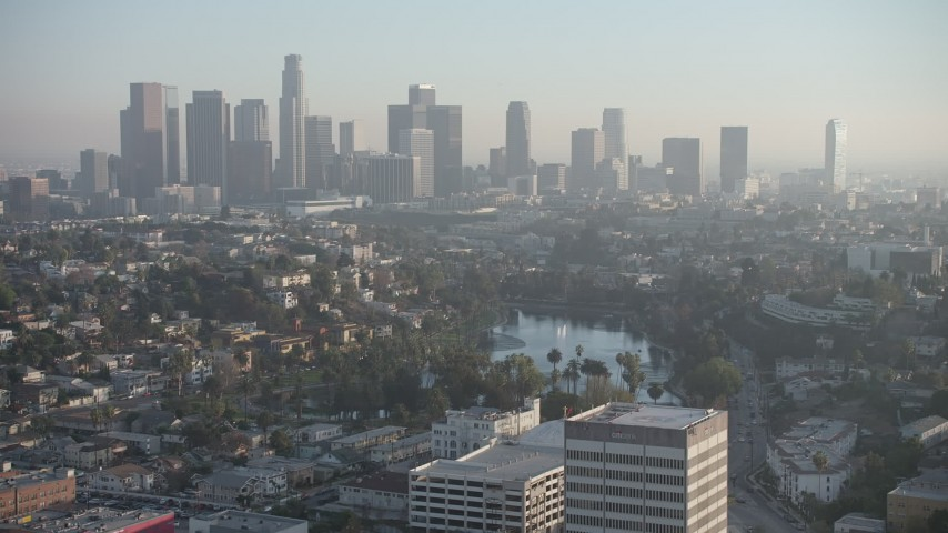 5K stock footage aerial video of an approach to Echo Park and hazy Downtown Los Angeles skyline, California Aerial Stock Footage | AX64_0078