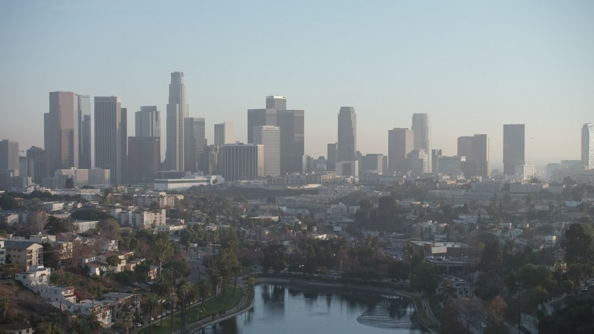 5K stock footage aerial video fly over Echo Lake to approach the Downtown Los Angeles skyline, California Aerial Stock Footage AX64_0081