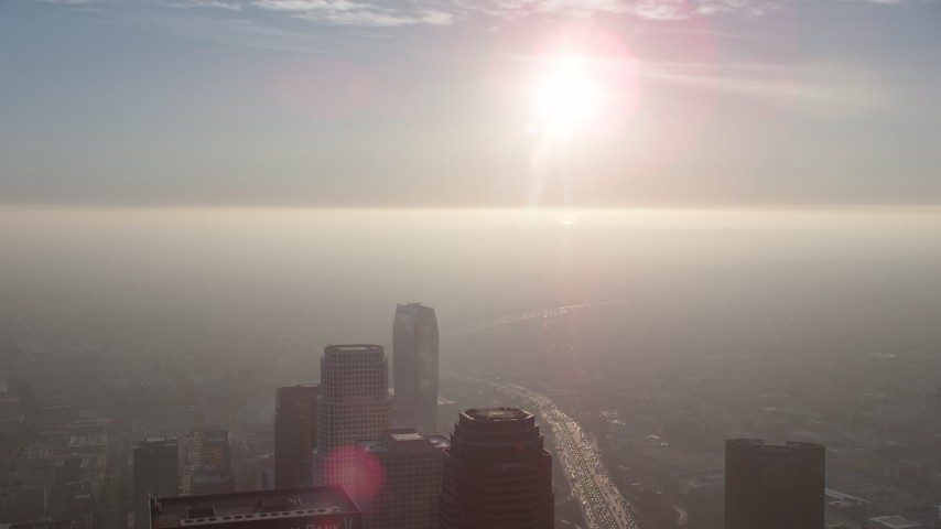 5K stock footage aerial video of sun over haze and skyscrapers in Downtown Los Angeles, California Aerial Stock Footage | AX64_0098