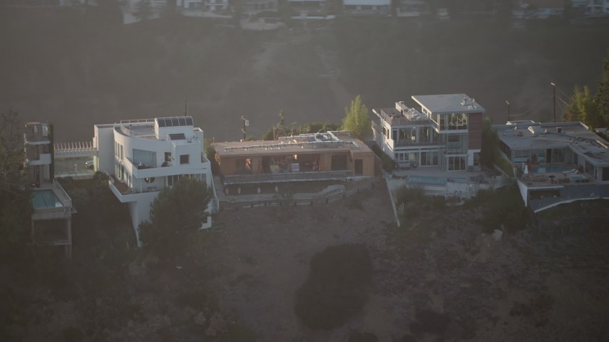 5K stock footage aerial video of passing hilltop mansions in Hollywood Hills, California Sunset Aerial Stock Footage   AX64_0123