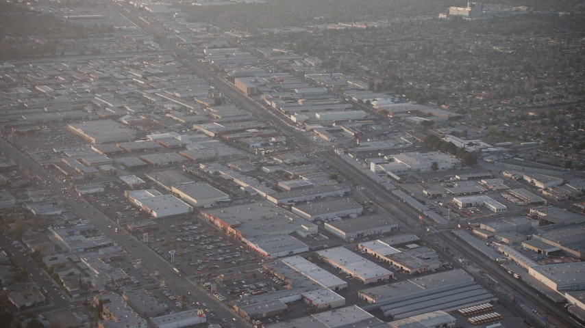 5K stock footage aerial video of warehouses and Sherman Way Square mall beside train tracks in North Hollywood, California, sunset Aerial Stock Footage | AX64_0134