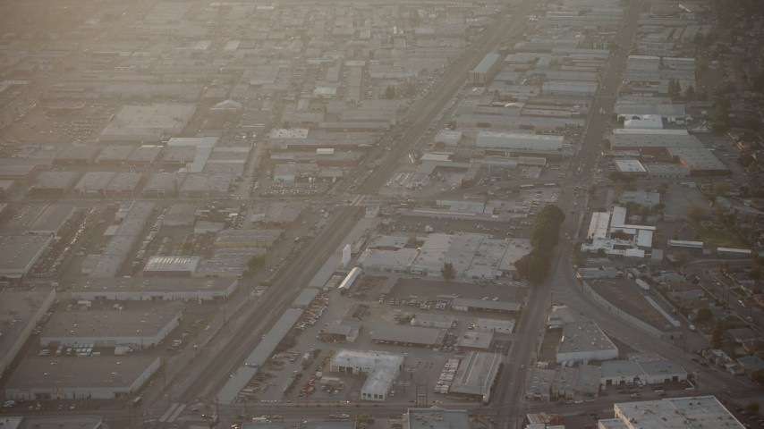 5K stock footage aerial video of warehouse buildings and railroad tracks in North Hollywood, California, sunset Aerial Stock Footage | AX64_0135