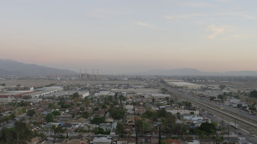 5K stock footage aerial video fly over warehouses to approach LADWP power plant in Pacoima, California, sunset Aerial Stock Footage | AX64_0143