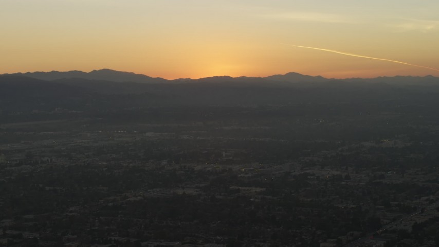 5K stock footage aerial video of sunset behind neighborhoods and the Hollywood Hills, California Aerial Stock Footage | AX64_0149
