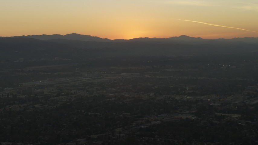 5K stock footage aerial video of suburban neighborhoods and the sun setting behind Hollywood Hills, California Aerial Stock Footage | AX64_0150