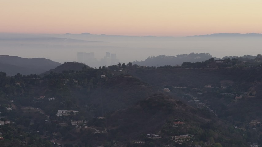 5K stock footage aerial video of Century City behind hilltop mansions in Hollywood Hills, California, twilight Aerial Stock Footage | AX64_0156