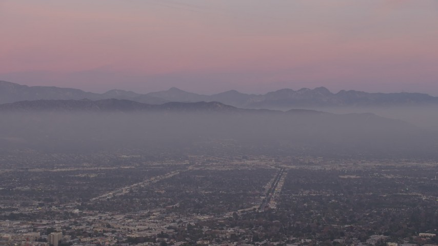 5K stock footage aerial video of Santa Susana Mountains and neighborhoods in San Fernando Valley, Los Angeles, California, twilight Aerial Stock Footage | AX64_0158