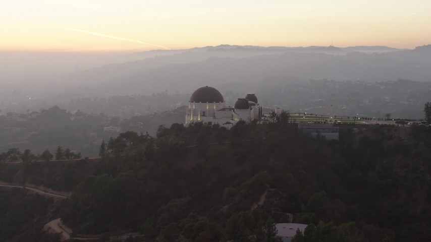 5K stock footage aerial video of reverse view of the Griffith Observatory, Los Angeles, California, twilight Aerial Stock Footage | AX64_0173