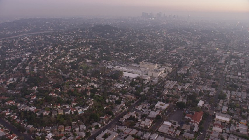 5K stock footage aerial video tilt from urban homes in Los Feliz, reveal Downtown Los Angeles, California, twilight Aerial Stock Footage | AX64_0175