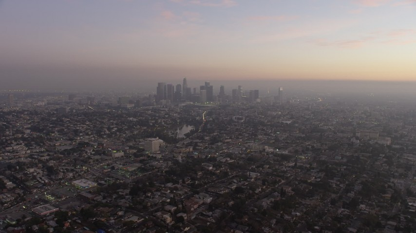5K aerial video of Downtown Los Angeles surrounded by city sprawl, California, twilight Aerial Stock Footage | AX64_0179