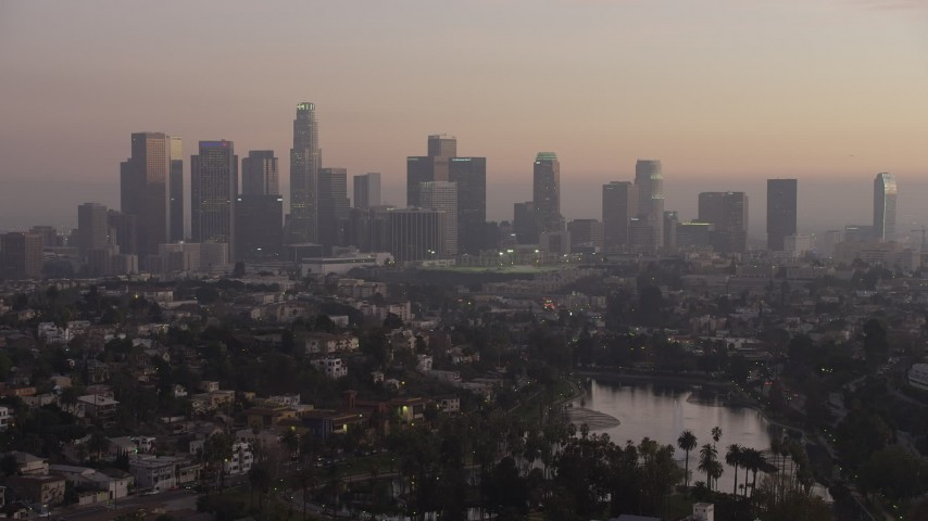 5K stock footage aerial video of Downtown Los Angeles in haze seen from Echo Lake at twilight, California Aerial Stock Footage | AX64_0181