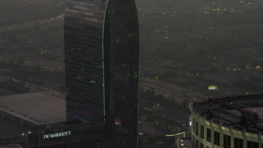 5K stock footage aerial video tracking a police helicopter flying over Downtown Los Angeles, California, twilight Aerial Stock Footage | AX64_0197