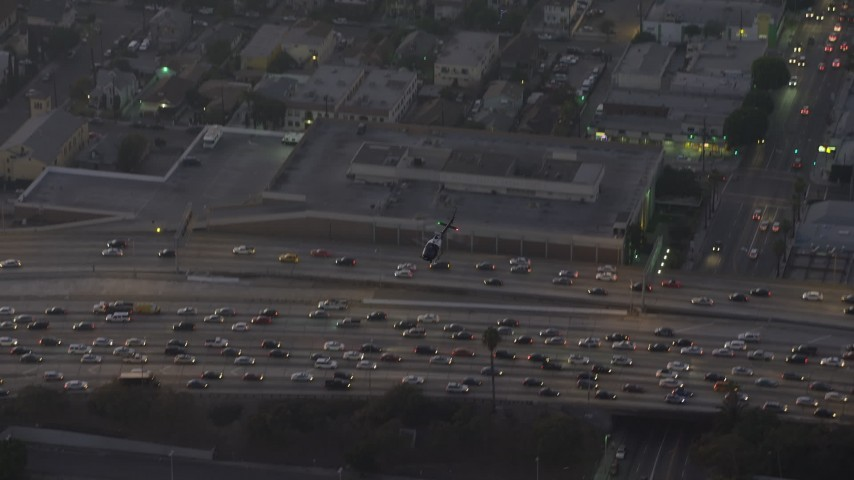 5K stock footage aerial video of a police helicopter flying over 110 freeway traffic in Downtown Los Angeles, California, twilight Aerial Stock Footage | AX64_0199