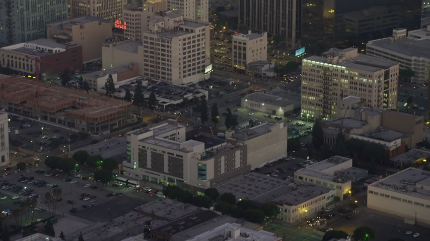 5K stock footage aerial video track a police helicopter flying over office buildings in Downtown Los Angeles, California, twilight Aerial Stock Footage | AX64_0200