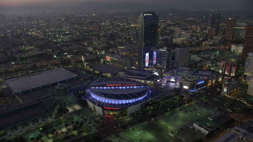 5K aerial video reverse view of Staples Center and The Ritz-Carlton, reveal skyscrapers in Downtown Los Angeles, California, twilight Aerial Stock Footage | AX64_0219