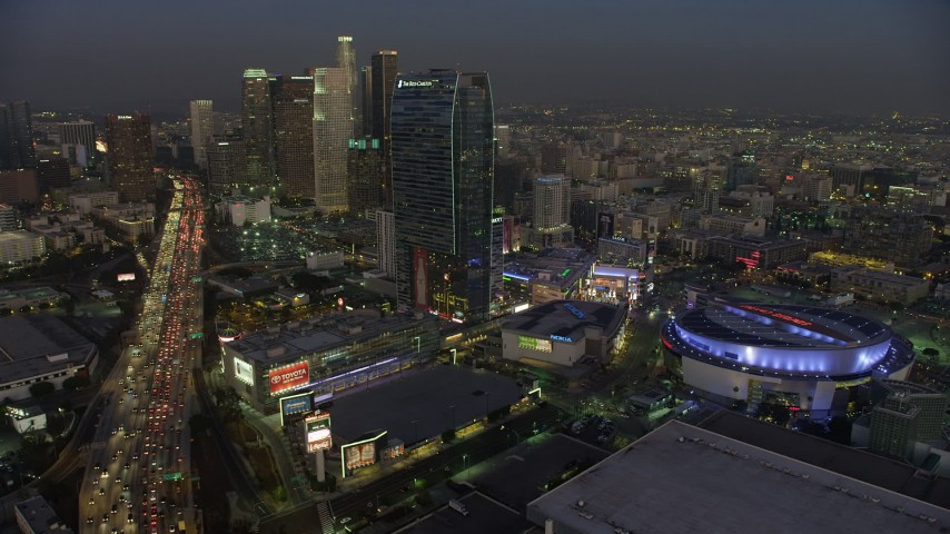 5K aerial video of 110 Freeway, Staples Center arena, and Downtown Los Angeles skyscrapers, California, twilight Aerial Stock Footage | AX64_0223