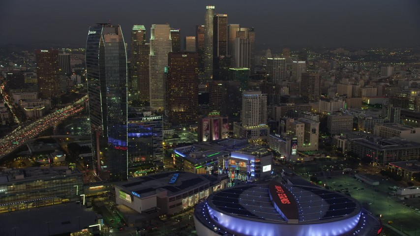 5K aerial video of passing Staples Center, Nokia Theater, Ritz-Carlton and skyscrapers, Downtown Los Angeles, California, twilight Aerial Stock Footage AX64_0225