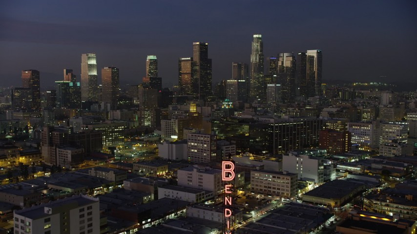 5K stock footage aerial video fly over the Bendix Sign to fly toward Downtown Los Angeles skyscrapers, California, twilight Aerial Stock Footage | AX64_0245