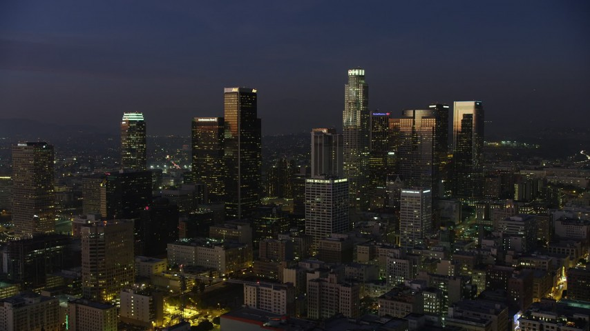 5K stock footage aerial video fly over Eastern Columbia Building to approach Downtown Los Angeles skyscrapers, California, twilight Aerial Stock Footage | AX64_0246