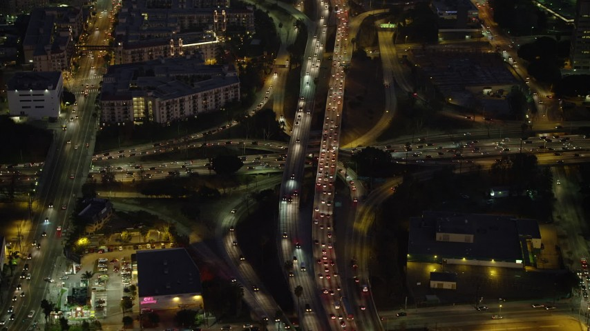 5K stock footage aerial video of reverse view of heavy traffic on 101 and 110 freeways in Downtown Los Angeles, California, Night Aerial Stock Footage | AX64_0253