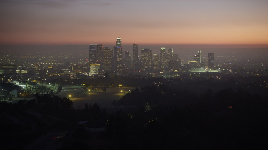 5K stock footage aerial video fly over hill to reveal the Downtown Los Angeles skyline, California, twilight Aerial Stock Footage | AX64_0258