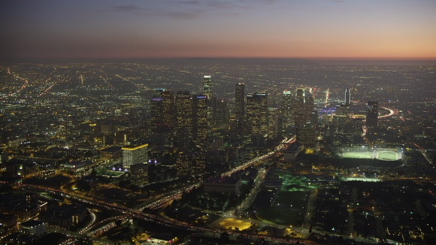 5K stock footage aerial video of tall skyscrapers and Highway 110 in Downtown Los Angeles, California at twilight Aerial Stock Footage | AX64_0263