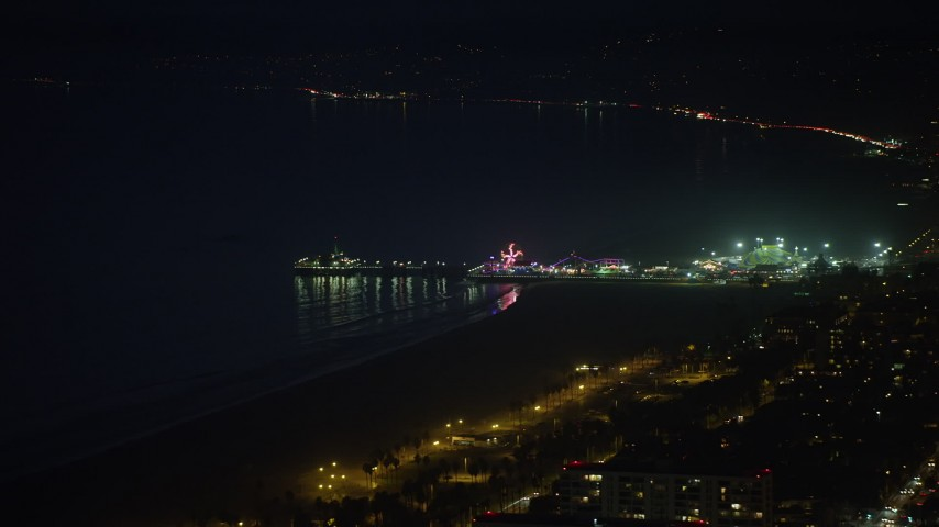 5K stock footage aerial video flyby the Santa Monica Pier with rides and ferris wheel at night, Los Angeles, California Aerial Stock Footage | AX64_0297