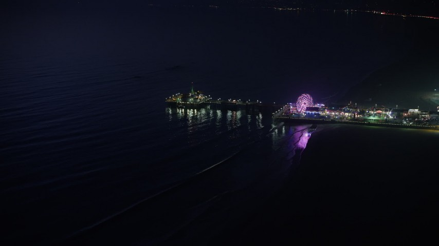 5K aerial video approach the end of Santa Monica Pier and the Pacific Wheel at night, Los Angeles, California Aerial Stock Footage | AX64_0300