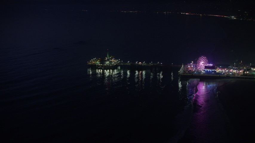Approach the end of Santa Monica Pier, Los Angeles, California, night Aerial Stock Footage | AX64_0301