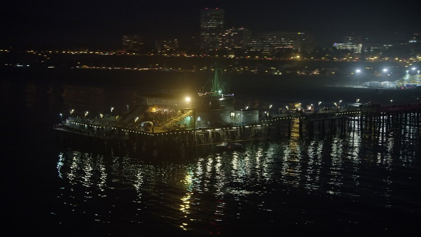5K stock footage aerial video flyby the end of Santa Monica Pier, Los Angeles, California, night Aerial Stock Footage | AX64_0302