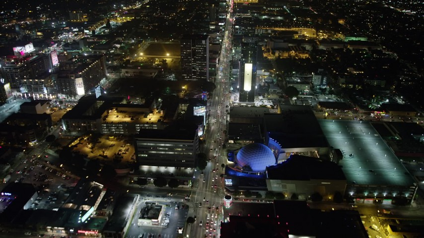 5K stock footage aerial video follow Sunset Boulevard and fly over ArcLight Hollywood, California, night Aerial Stock Footage | AX64_0337
