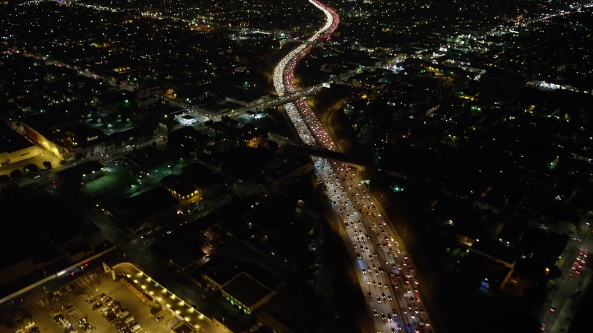 5K stock footage aerial video tilt from Highway 101 to reveal the Downtown Los Angeles skyline, California. night Aerial Stock Footage | AX64_0340