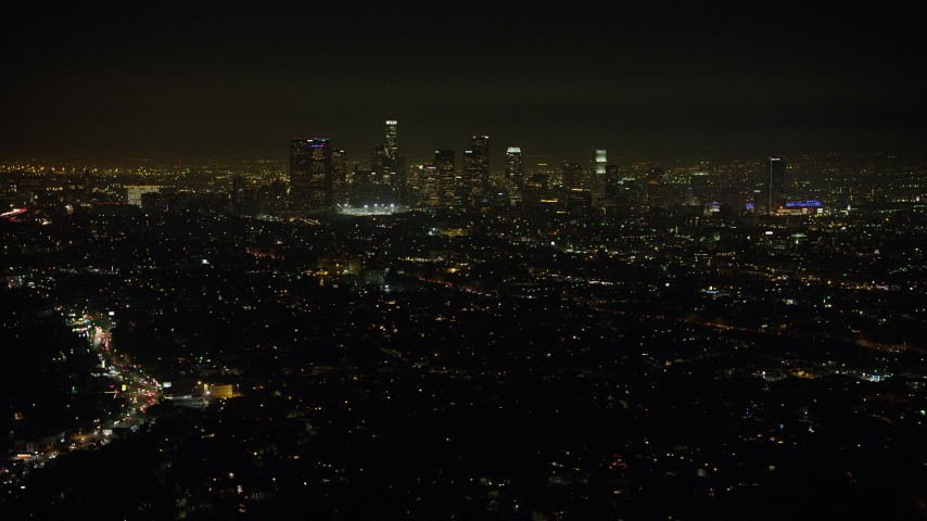 5K stock footage aerial video of flying by the Downtown Los Angeles skyline and city sprawl, California, night Aerial Stock Footage | AX64_0345