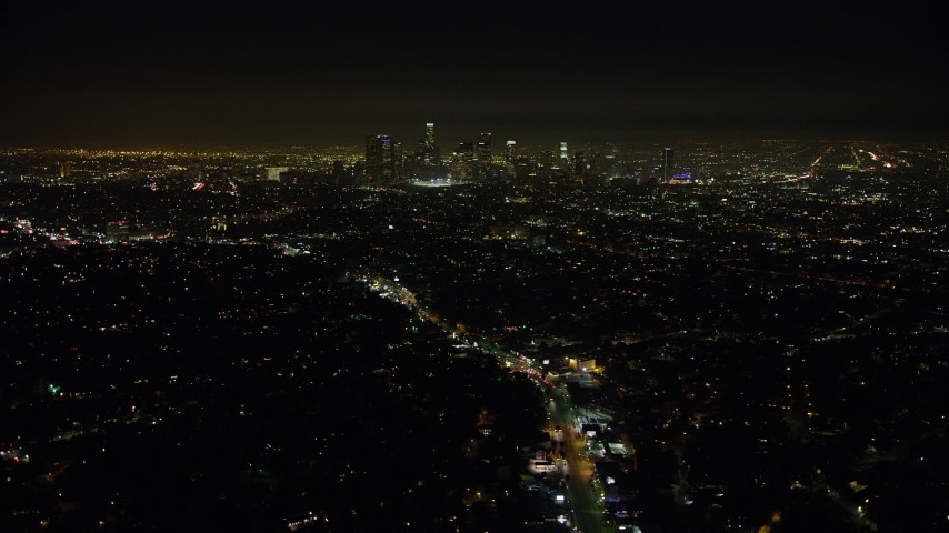 5K stock footage aerial video of a view of the Downtown Los Angeles skyline and surrounding city sprawl, California, night Aerial Stock Footage | AX64_0346