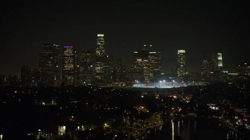 5K stock footage aerial video of a view of the Downtown Los Angeles skyline from Echo Lake at night, California Aerial Stock Footage | AX64_0352