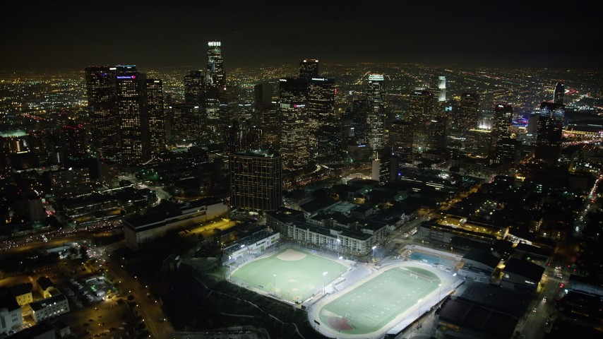 5K aerial video fly over high school sports fields to approach Downtown Los Angeles skyscrapers, California, night Aerial Stock Footage | AX64_0356